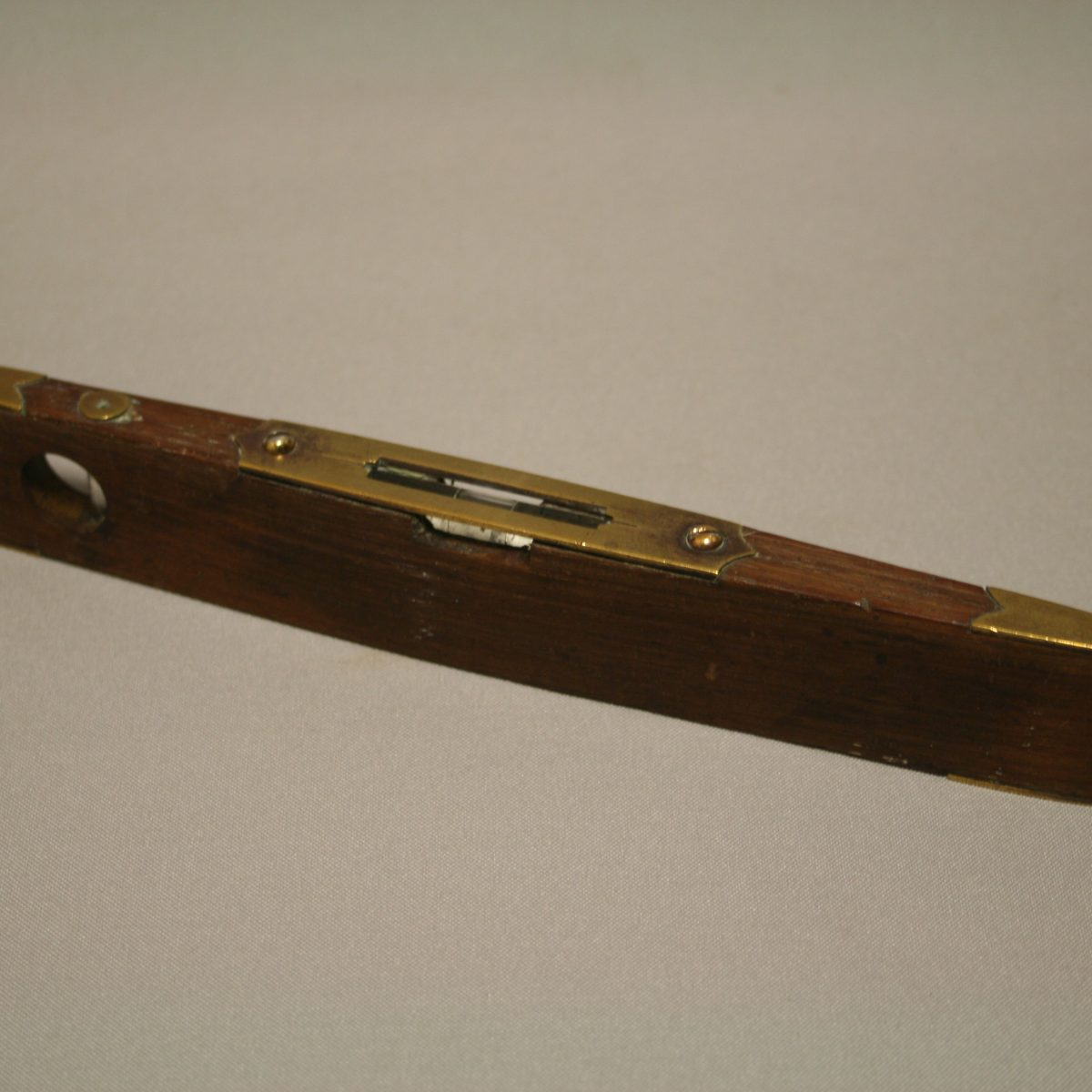 A wooden spirit level with brass detailing