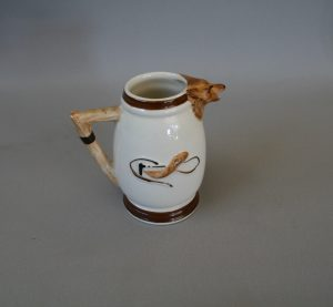 A small cream jug with a hunting scene. Made by Keele Street Pottery, England.