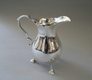 A dainty silver cream jug standing on three shaped legs/williamsantiques